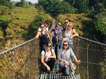 foreign volunteers taking picture in an suspension bridge