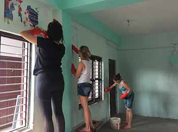 foreign volunteers painting walls of a class in nepal