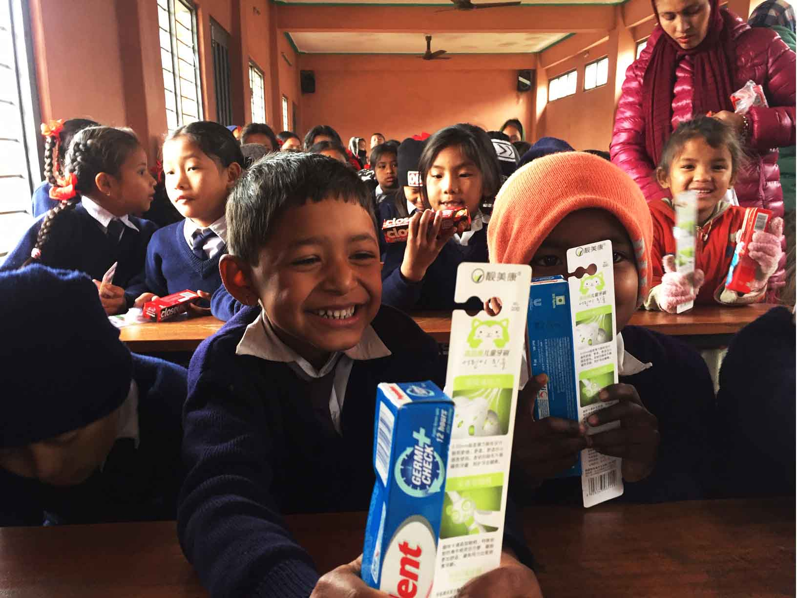 handing out toothbrush and toothpaste to happy children by volunteers