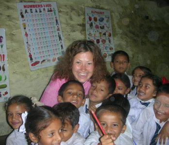happy volunteer foreign teacher with students in nepal