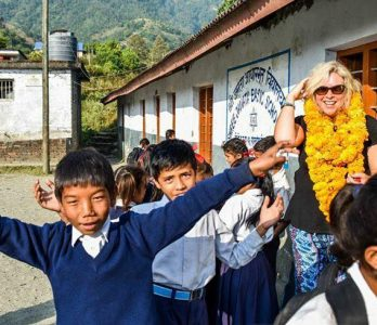 students of rural area in nepal welcoming a foreign with flowers